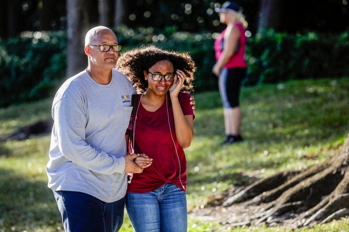 A father and daughter walking with each other following the tragedy at Marjory Stoneman Douglas High School.