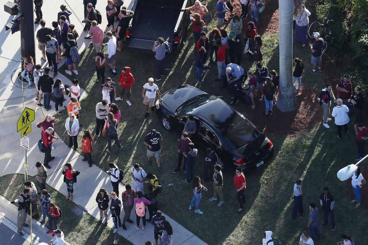 People waiting for loved ones as they are brought out of Marjory Stoneman Douglas High School.