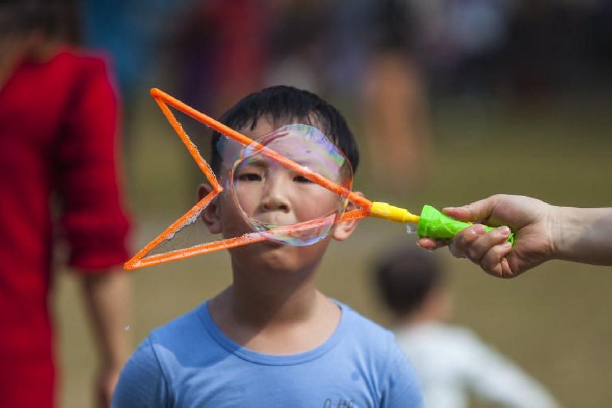 A boy blows soap bubbles in Liwan Park on the first day of the Lunar New Year in Guangzhou, Guandong Province, China, on Feb 16, 2018.