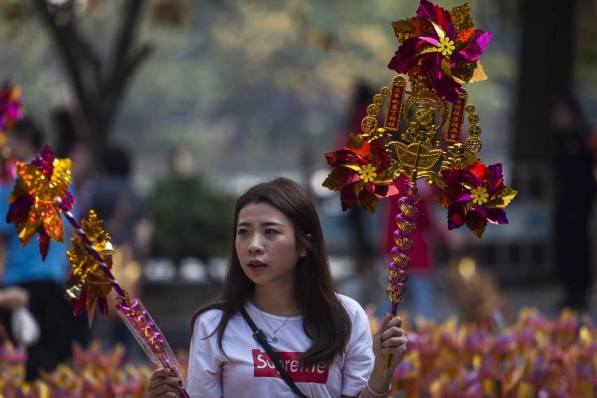 A Chinese Buddhist buys Buddhist religious and decorative ornaments at the Renwei Temple to mark the first day of the Lunar New Year in Guangzhou, Guandong Province, China, on Feb 16, 2018.