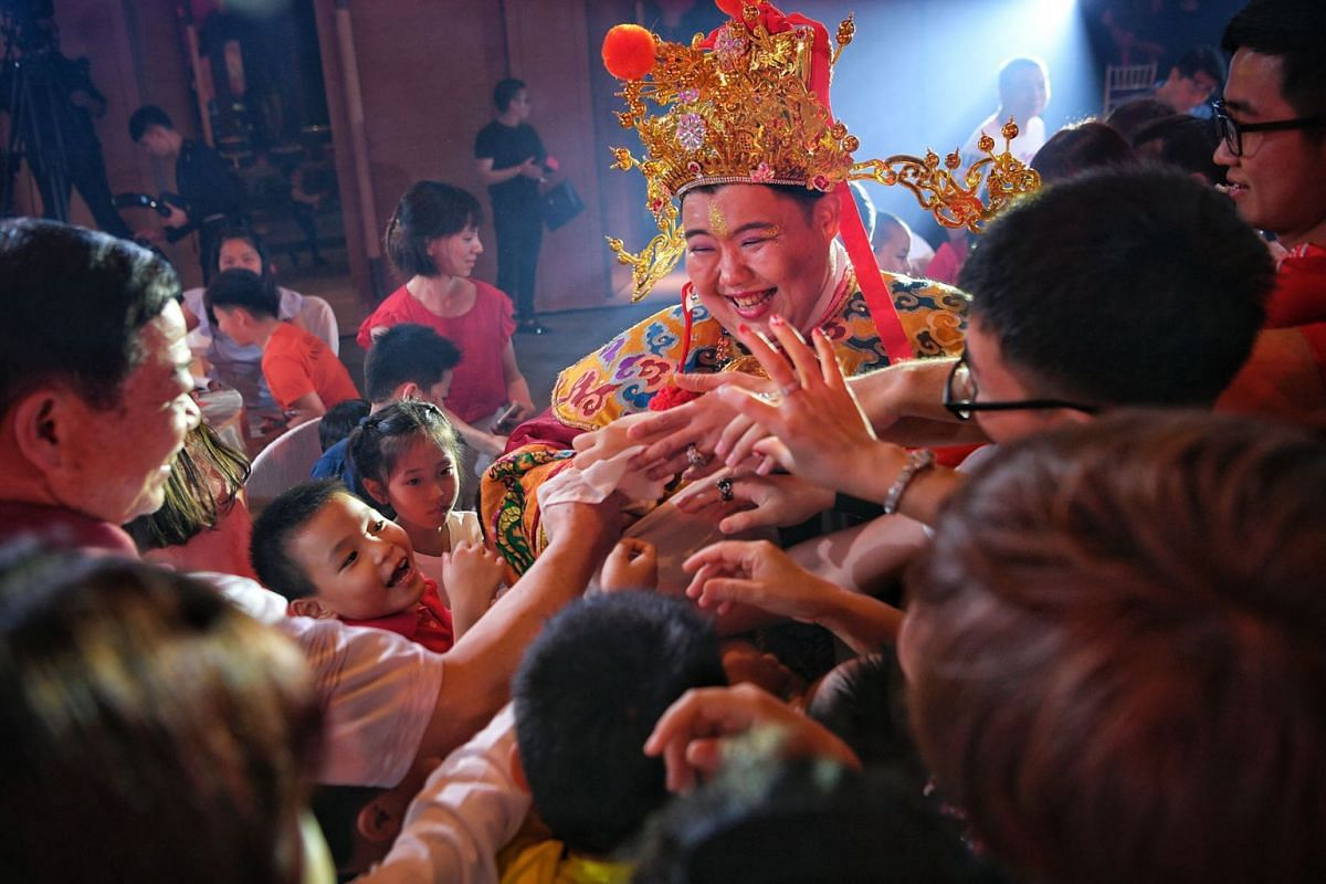 A photo released today Feb 19, 2018, shows Mr Alec Chia dressed up as the God of Fortune and handing out red packets filled with sweets and lucky numbers to children at Sentosa's Capella Singapore hotel on Feb 15, 2018. PHOTO: THE STRAITS TIMES/MAR