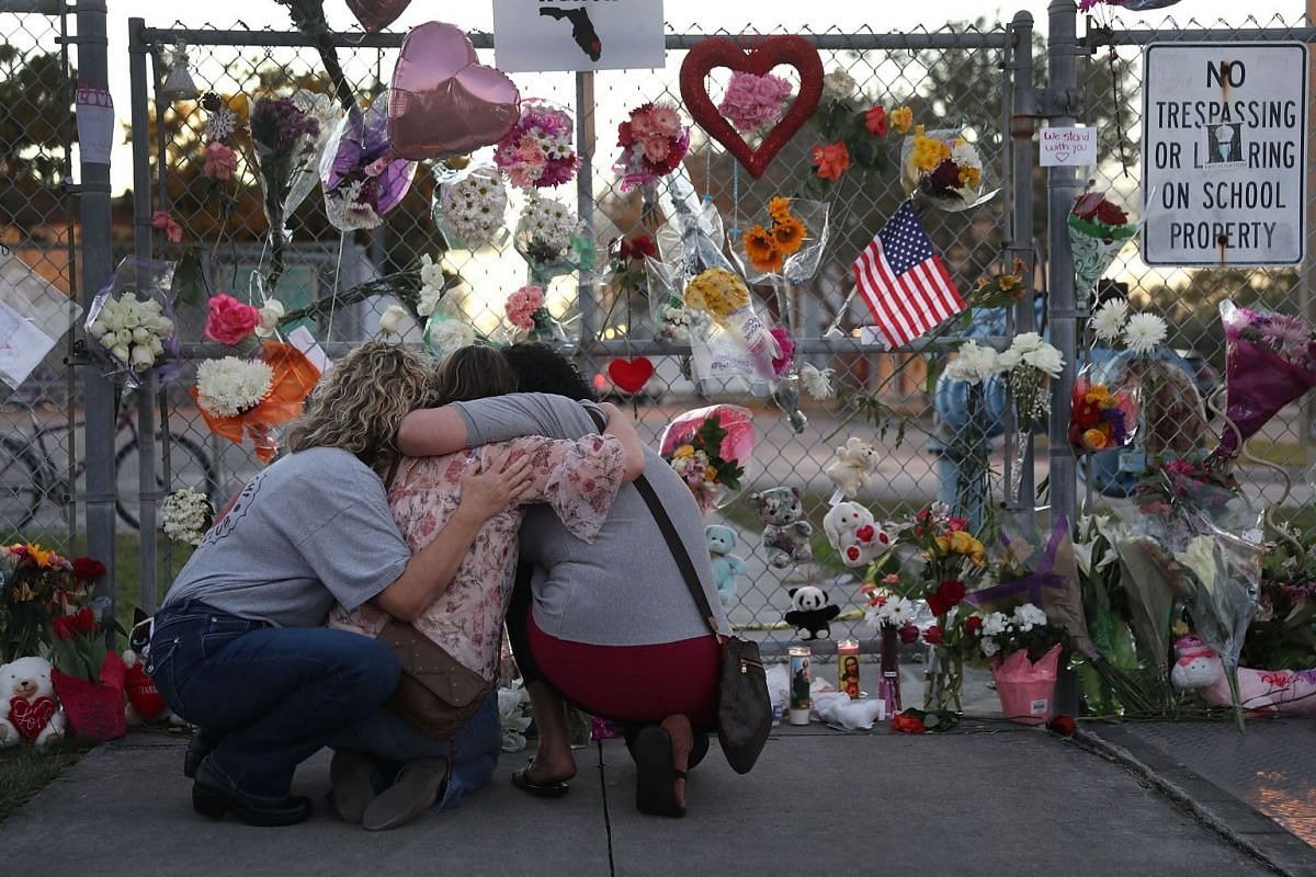 Shari Unger, Melissa Goldsmith and Giulianna Cerbono (L-R) hug each other as they visit a makeshift memorial setup in front of Marjory Stoneman Douglas High School on February 18, 2018 in Parkland, Florida. PHOTO: GETTY IMAGES/ AFP