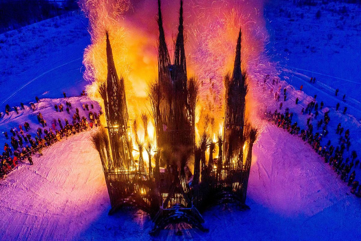An aerial view taken with a drone on February 17, 2018 shows spectators as they watch the burning of a thirty-meter structure built of twigs and debris made in the form of a Gothic style building by Russian artist Nikolay Polissky during the celebrat