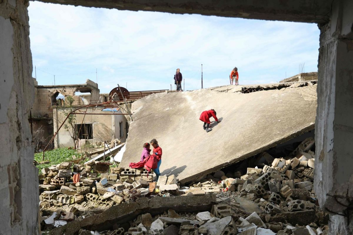 Syrian children play outside their destroyed school in the Frikeh village, in Idlib's Western countryside on February 18, 2018. PHOTO: AFP