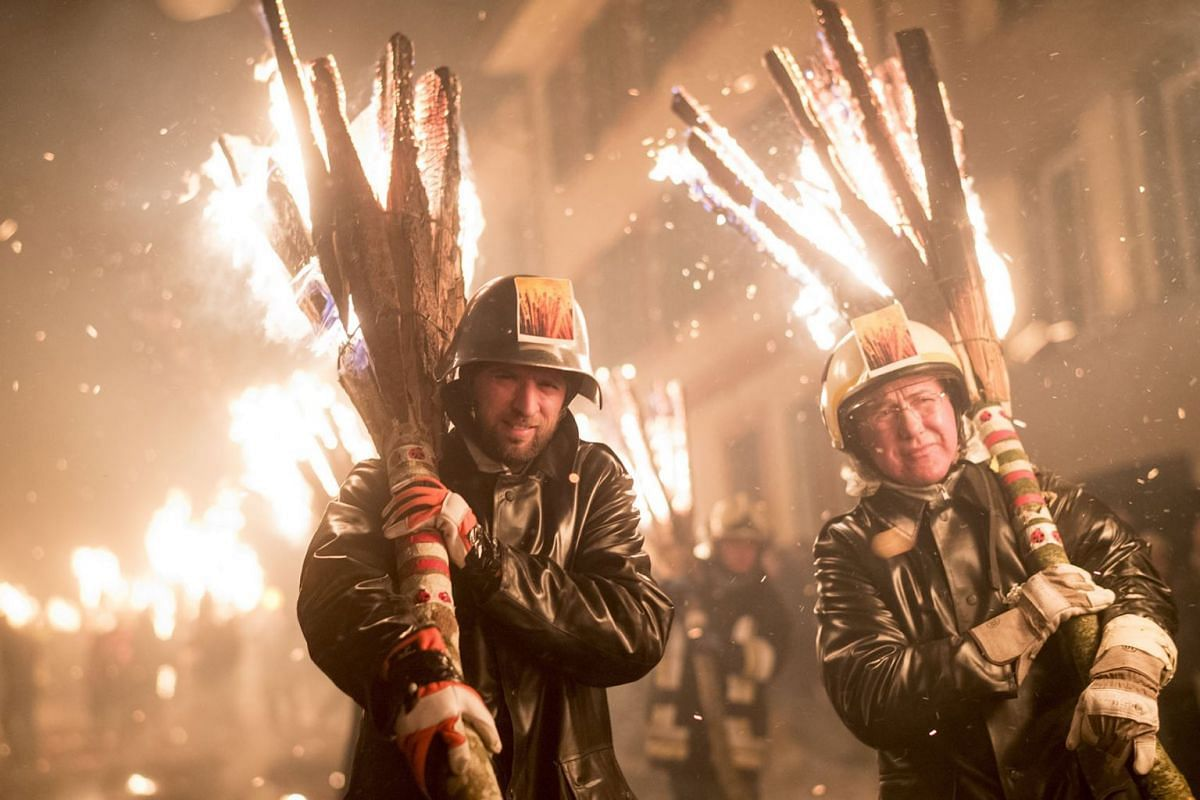 Men walk at the torchlight procession called 'Chienbaese' in Liestal near Basel, Switzerland, February 18, 2018. The procession continues through the dark lanes of the old town, bringing the light and the hope of warmer days to the city residents. PH
