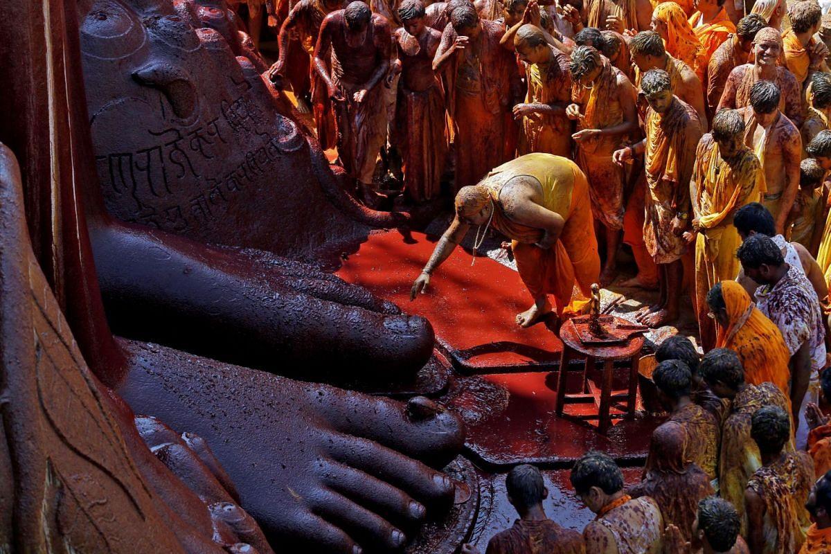A devotee touches the feet of the monolithic statue of Jain god Gomateshwara as he celebrates the Mahamastakabhisheka, or head-anointing ceremony of the statue, in Shravanabelagola, India, February 18, 2018. PHOTO: REUTERS