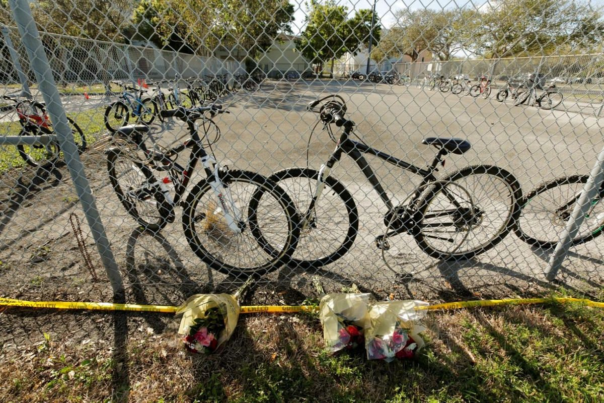 Flowers left by a fence beside bicycles that were used to go to school on the day of the shooting at Marjory Stoneman Douglas High School.