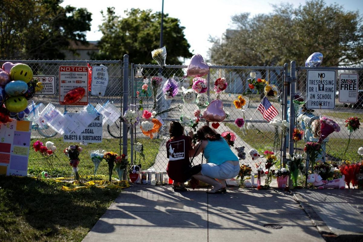 People put flowers and other mementoes at the fence of Marjory Stoneman Douglas High School.