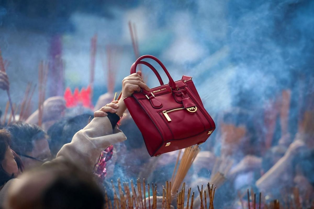 A woman waves her handbag in circles over burning incense for good luck during Chinese New Year celebrations in Hong Kong.