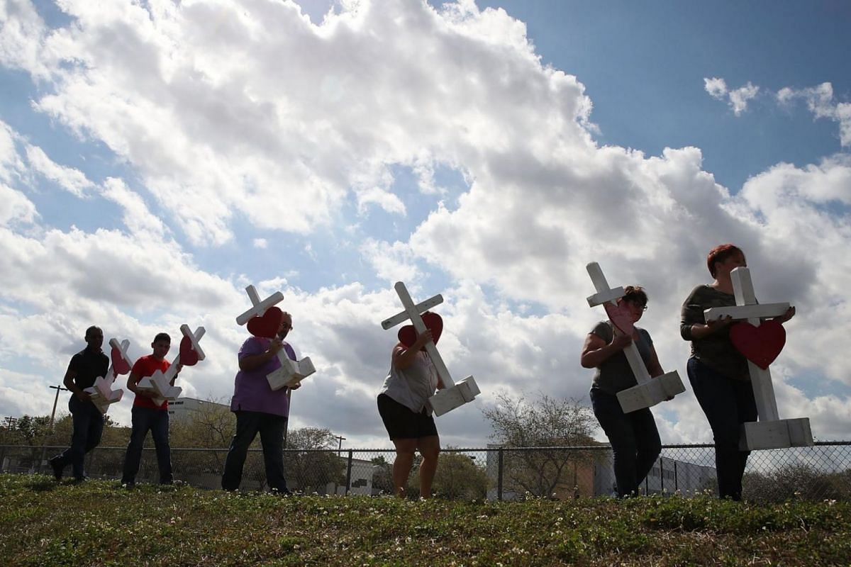 Volunteers carry crosses to be placed in front of Marjory Stoneman Douglas High School where 17 people were killed.
