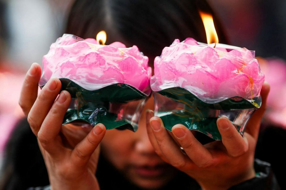 A woman holds candles as she prays at a Buddhist temple in Badachu Park, China.