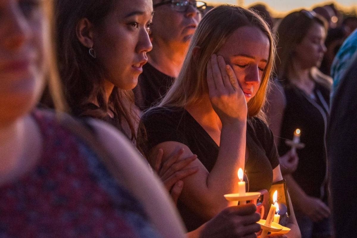 Hundreds of community members take part in a candlelight vigil at the Amphitheatre at Pine Trails Park in Parkland, Florida.