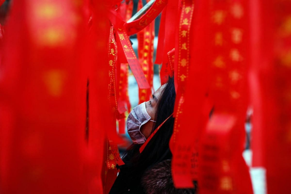 A Chinese woman looks at ribbons on trees at Badachu Park during Chinese New Year celebrations in China.