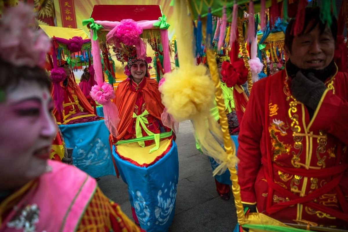 Chinese performers rest before their performance at Badachu Park as part of celebrations in China.