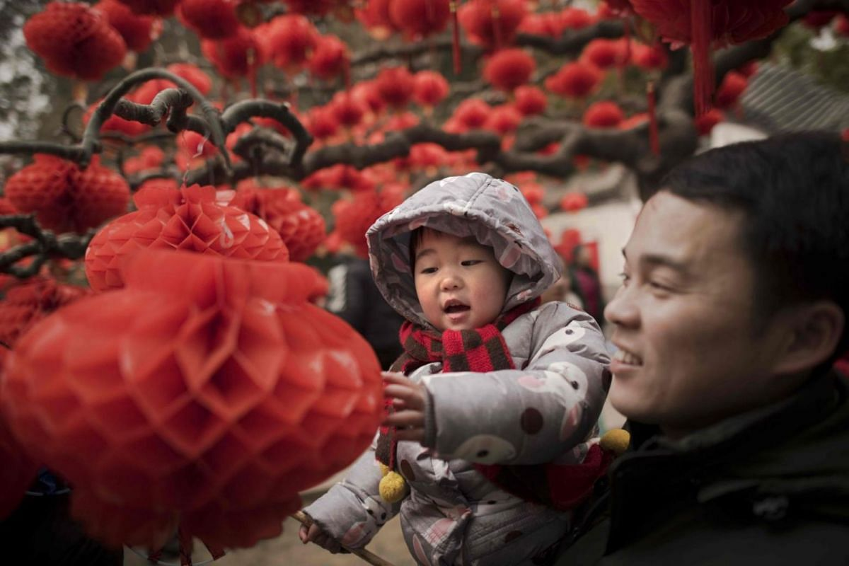 A man holds a child next to a tree decorated with lanterns at a fair to celebrate the Chinese New Year in Beijing, China.