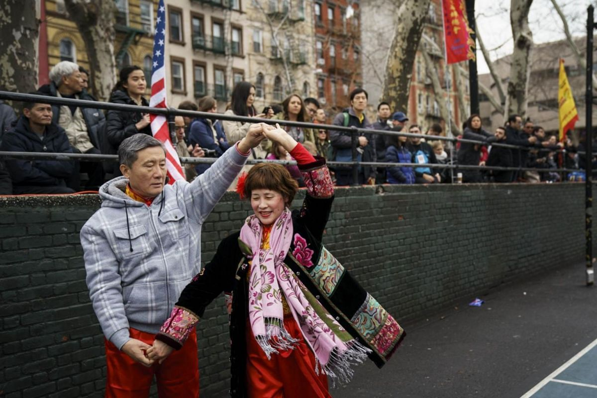 People dance before the start of a firecracker ceremony and cultural festival to mark the first day of the  New Year in Manhatten, New York.