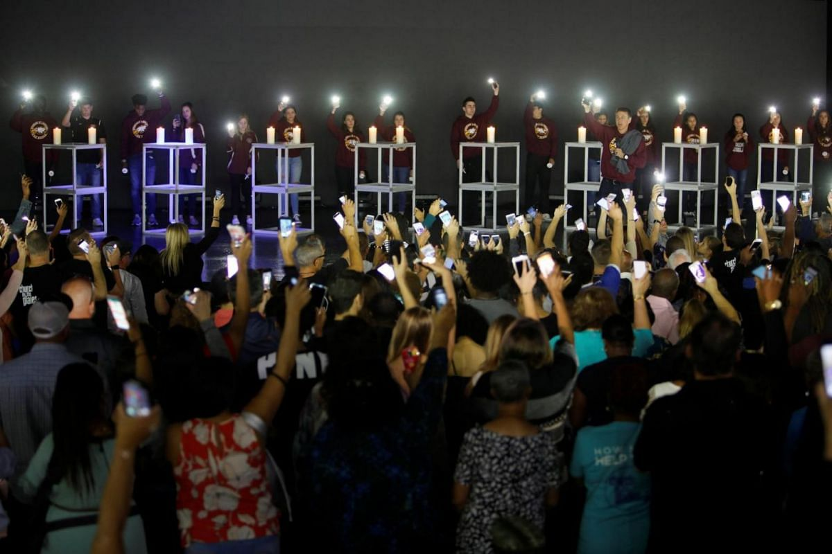 Local students, including some from Marjory Stoneman Douglas High School, hold up their phone lights in front of the congregation at the Church By The Glades at the end of a vigil for victims of the school shooting.