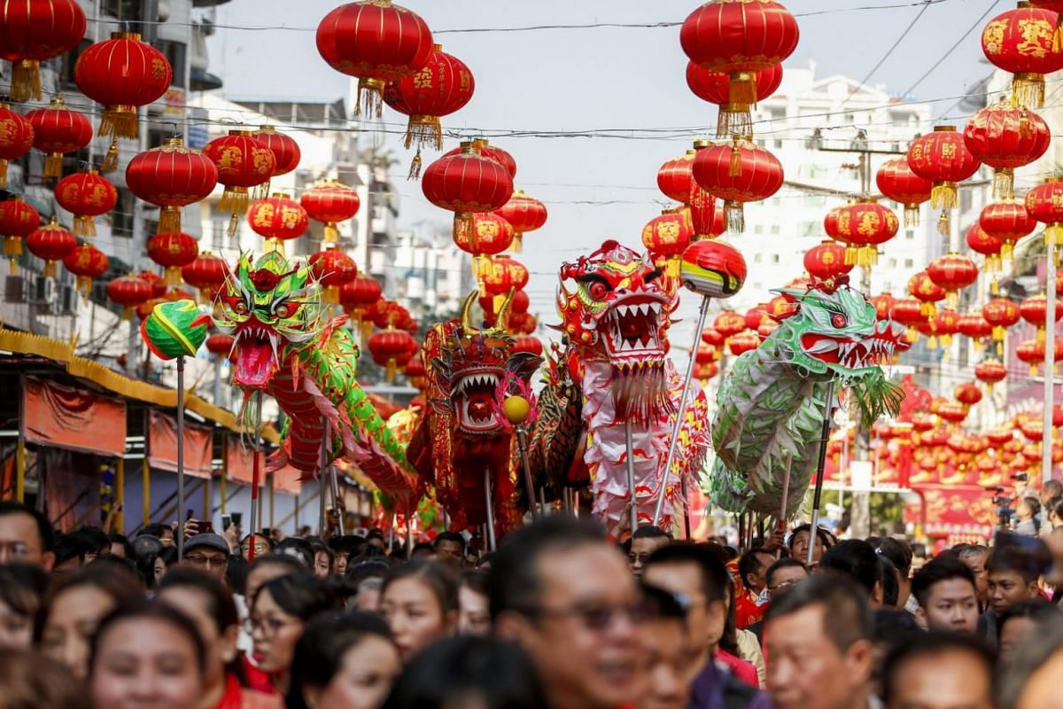 Dragon dancers march with people during Chinese New Year celebrations at Chinatown in Yangon, Myanmar.