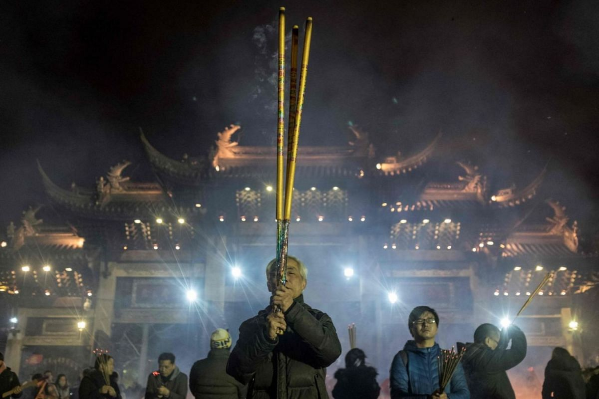 People pray with incense sticks to celebrate the Chinese New Year at the Longhua temple in Shanghai.