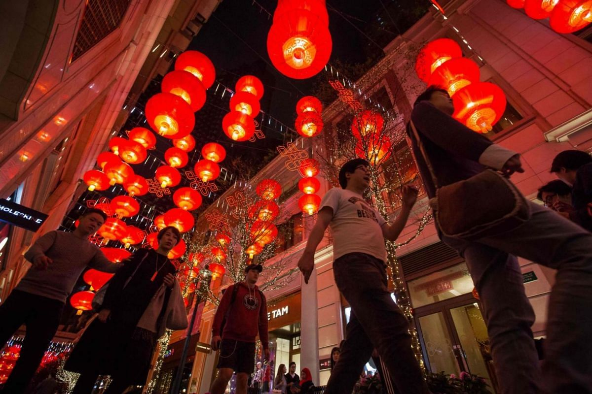 Pedestrians walk beneath red lanterns hung up over a street during Chinese New Year celebrations in Hong Kong.