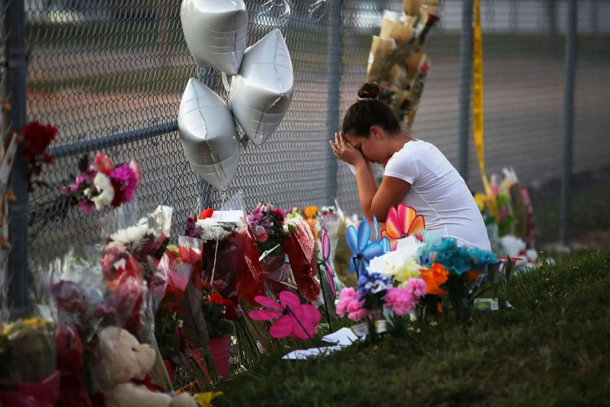 Shana Rosenthal, a student at Marjory Stoneman Douglas High School, visits a makeshift memorial set up in front of the school on Feb 18, 2018.