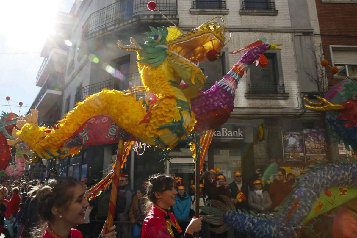 People take part in a traditional dragon parade to frighten off evil spirits during celebrations to mark the Chinese New Year in Madrid, Spain.
