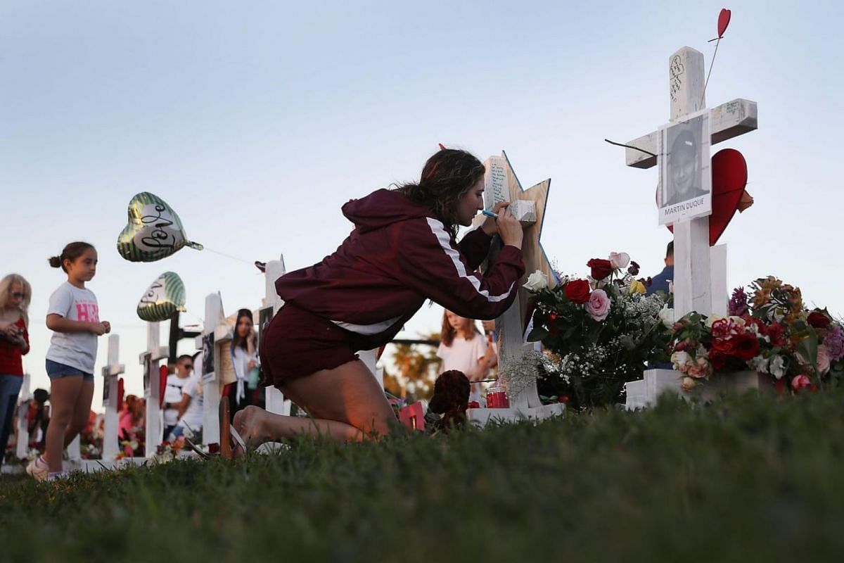 Rebecca Bogart, a senior at Marjory Stoneman Douglas High School, writes a note on a makeshift memorial.