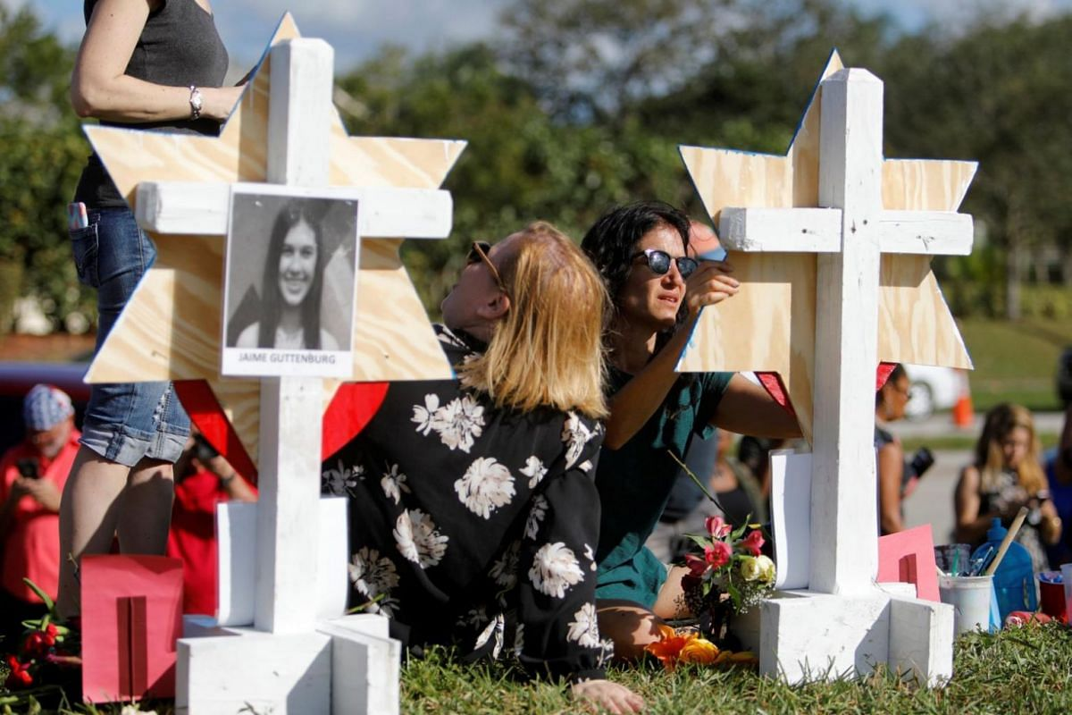 A community member writes on a Star of David for one of the victims of the shooting at Marjory Stoneman Douglas High School.