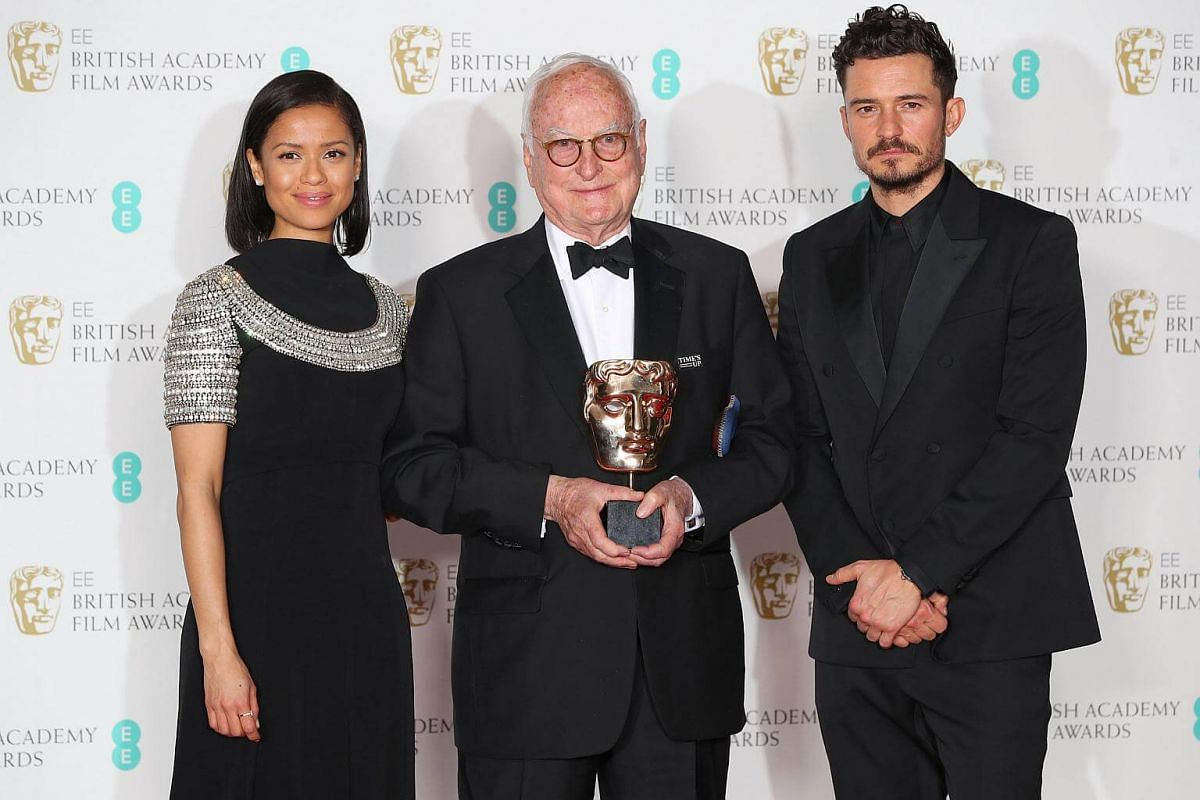 Presenters Orlando Bloom and Gugu Mbatha-Raw stand with James Ivory as he holds his award for Adapted Screenplay for Call Me By Your Name at the British Academy of Film and Television Awards at the Royal Albert Hall in London, on Feb 18, 2018.