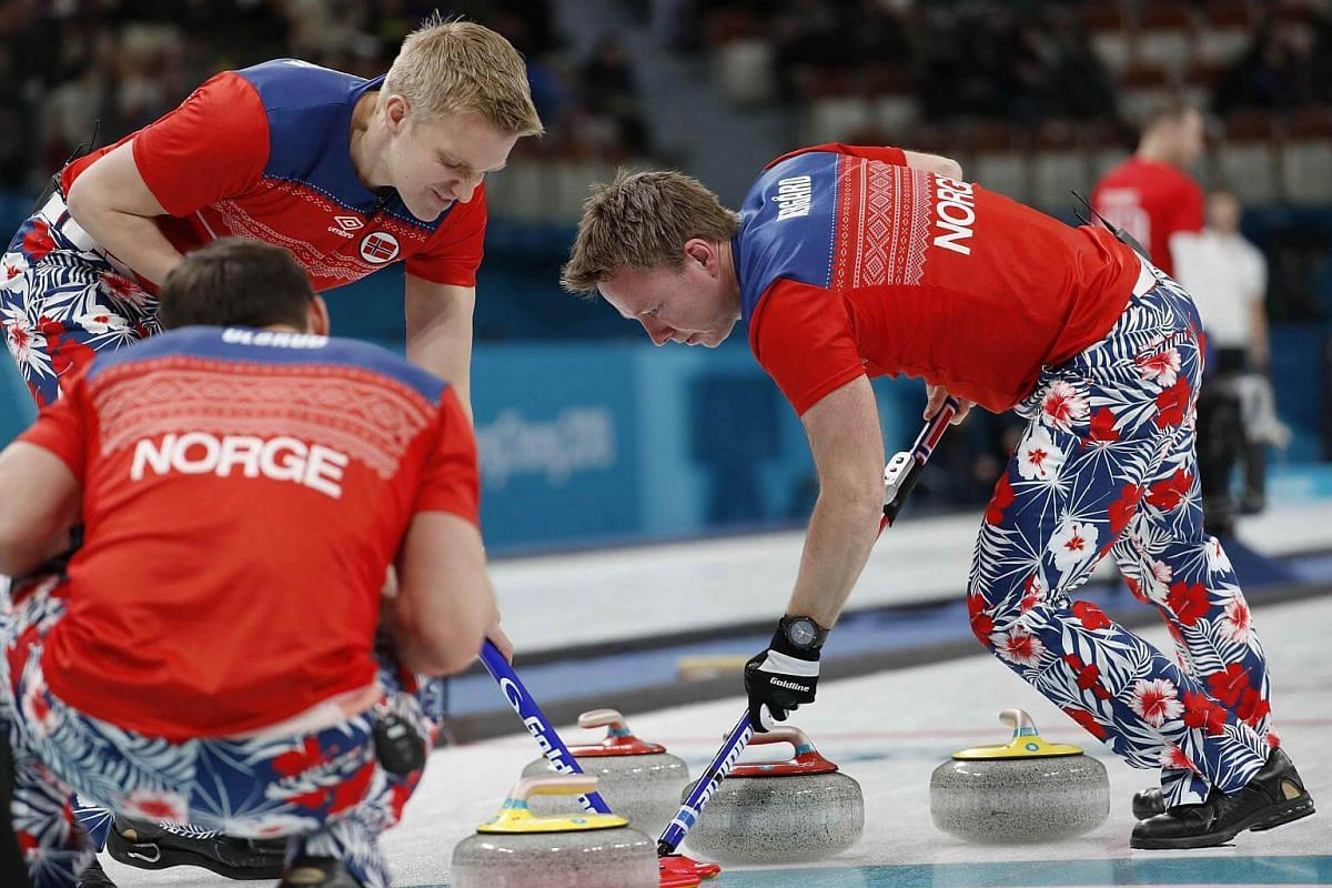 Lead Haavard Vad Petersson and vice-skip Torger Nergaard of Norway sweep.
