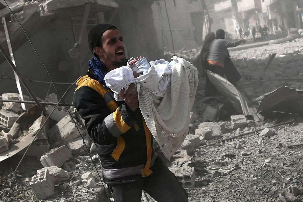 A Syrian man carries an infant rescued from the rubble of buildings following government bombing in the rebel-held town of Hamouria, on the outskirts of the capital Damascus, on Feb 19, 2018.