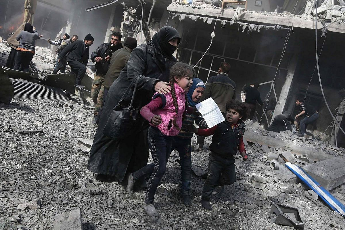 A Syrian woman and children run for cover amid the rubble of buildings following government bombing in the rebel-held town of Hamouria, on the outskirts of the capital Damascus, on Feb 19, 2018.