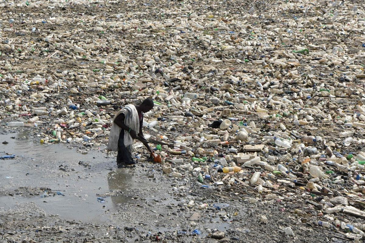 A man collects plastic from a waste water evacuation canal in the Ebrie Lagoon in Abidjan on Feb 19, 2018, before hawking his catch at a market.