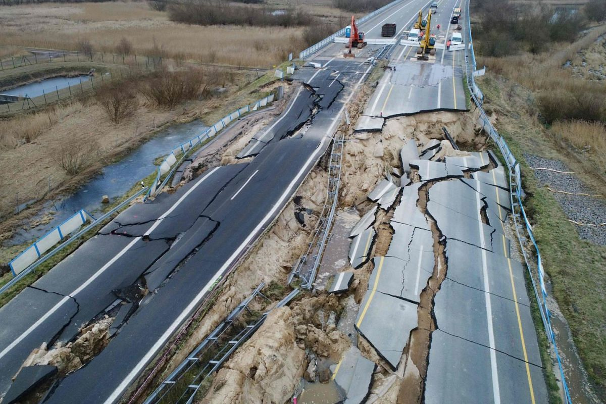 Excavators getting ready to dismantle the road dam on the cut-off section of the A20 motorway at the site of an unexplained landslide near Tribsees, northern Germany, on Feb 19, 2018.