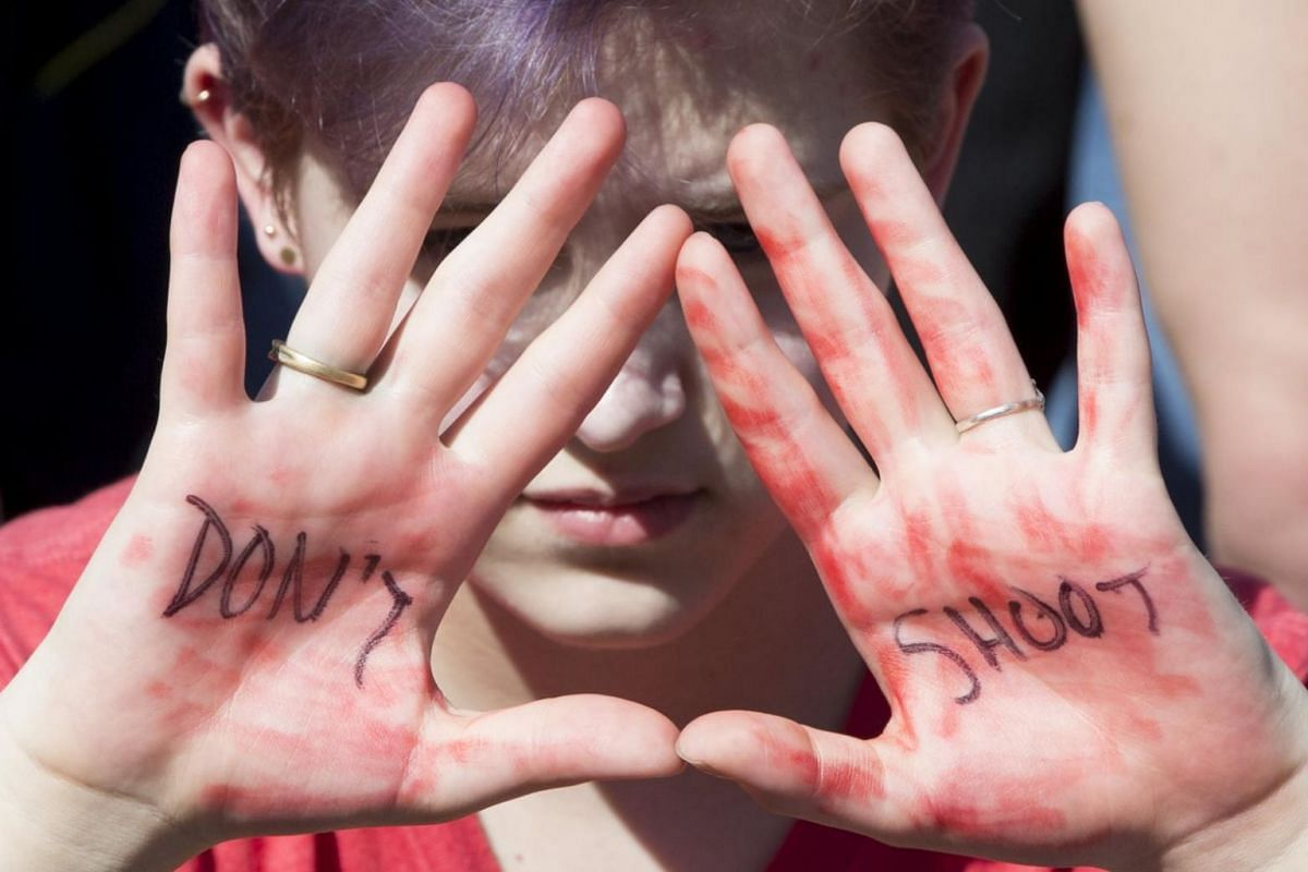 A young woman holds up her hands with words that read 'don't shoot' as students demonstrate for stronger gun control laws outside the White House in Washington, DC.