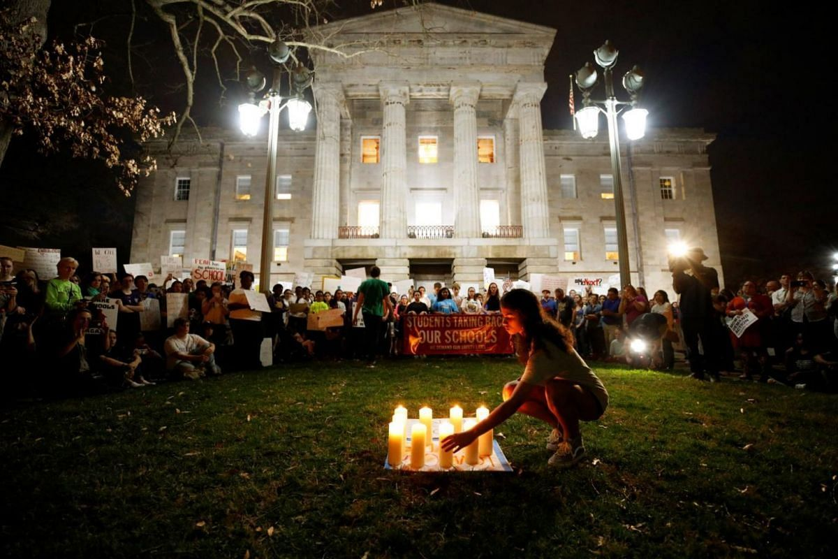 A high school student places a candle representing one of the victims of the shooting at Marjory Stoneman Douglas High School outside the North Carolina State Capitol building during a demonstration calling for safer gun laws, in Raleigh, North Carol