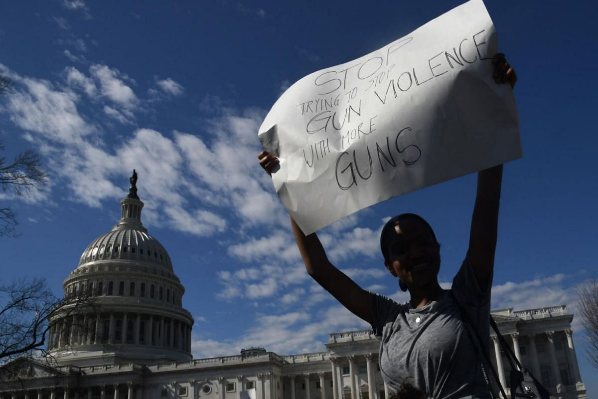 A student hoists a sign outside the Capitol building in support of gun control after the shooting at Marjory Stoneman Douglas High School on Feb 21, 2018.