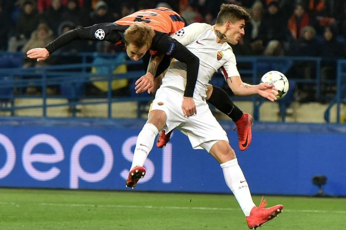 Shakhtar Donetsk's defender Bohdan Butko (L) fights for the ball with Roma's Argentinian midfielder Diego Perotti during the UEFA Champions League round of 16 first leg football match between Shaktar Donetsk and AS Rome at The OSK Metalist Stadion in