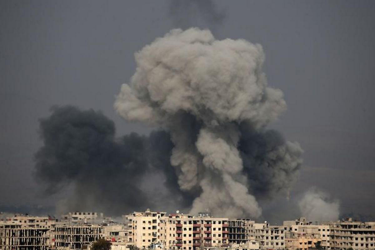A picture taken on Feb 20, 2018 shows smoke plumes rising following a reported regime air strike in the rebel-held town of Hamouria, in the besieged Eastern Ghouta region on the outskirts of the capital Damascus, Syria.