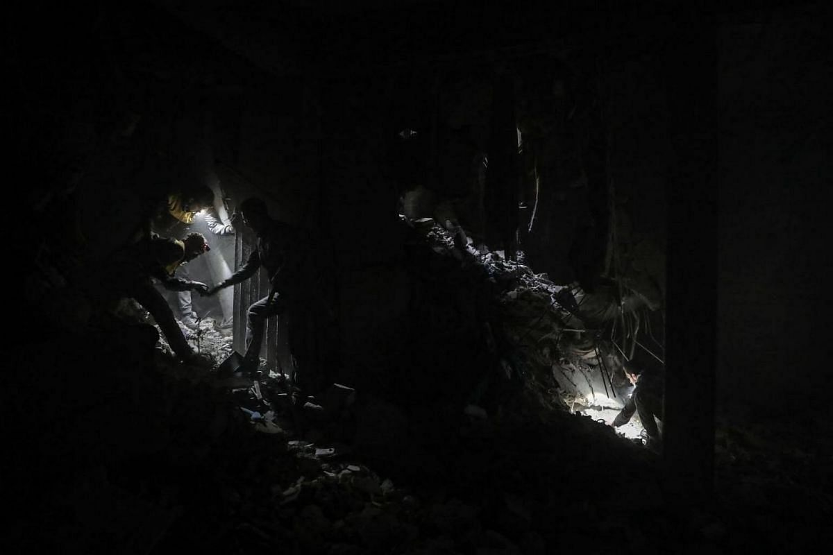 White helmet volunteers and civilians search for survivors among the rubbles after bombing, in the rebel-held Douma, Eastern Ghouta, Syria, Feb 22, 2018. More than 42 people got killed in Douma after several airstrikes and shelling by forces allegedl