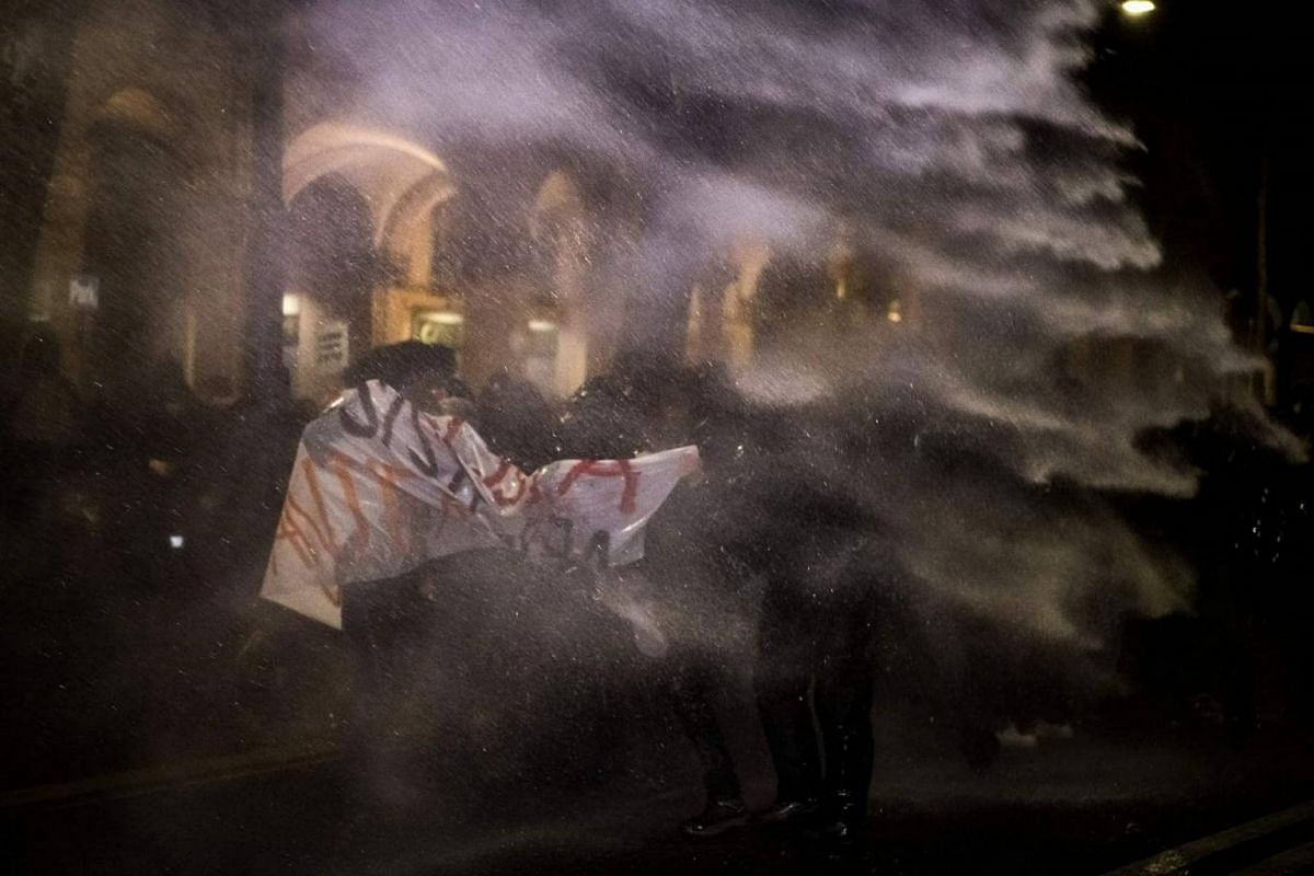Anti-fascist activists protect themselves from a water cannon used by police officers during a rally against an election campaign meeting organized by far-right movement CasaPound, on Feb 22, 2018 in Turin.