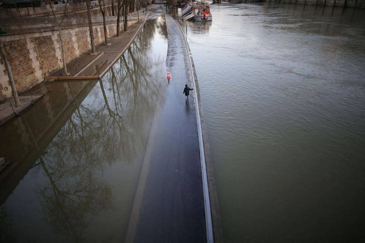 A young boy walks along the flooded banks of the Seine River in Paris, France, on Feb 22, 2018.