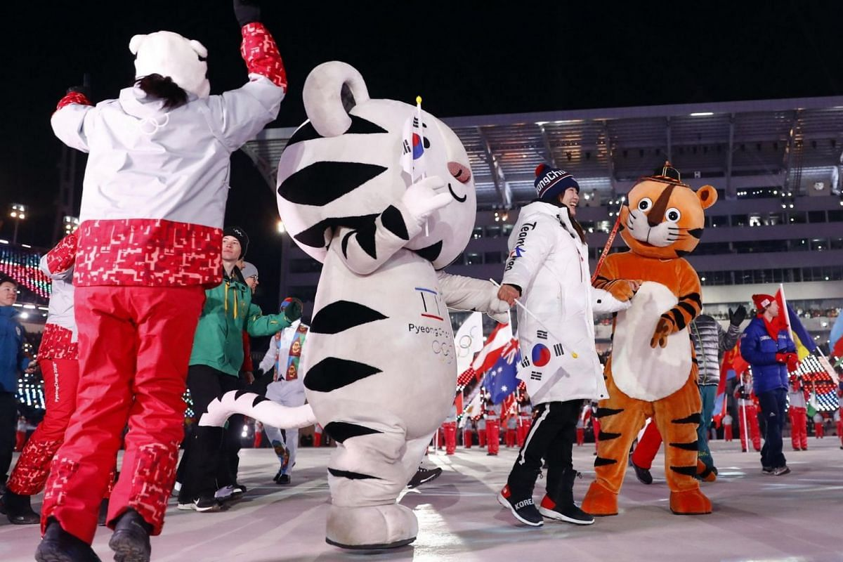 Soohorang and Hodori, mascots of the 2018 Winter Olympics, dance with a member of the delegation of the unified Korea team during the closing ceremony.