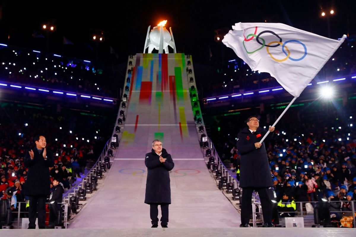 International Olympic Committee President Thomas Bach applauds after handing over the Olympic flag to Beijing mayor Chen Jining as Pyeongchang mayor Shim Jae Kook looks on during the closing ceremony of the Pyeongchang 2018 Winter Olympic Games.