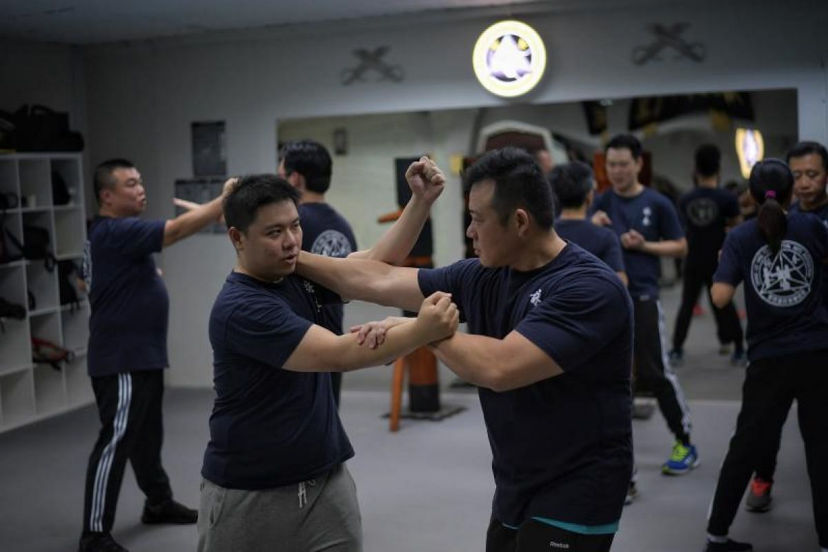 Wing chun students Tan Jin Kiat (right), 44, and Ken Tan (left), 31, practising moves during a class at Dennis Lee Ving Tsun Martial Arts Association (Singapore) at Selegie Road on Feb 21, 2018.