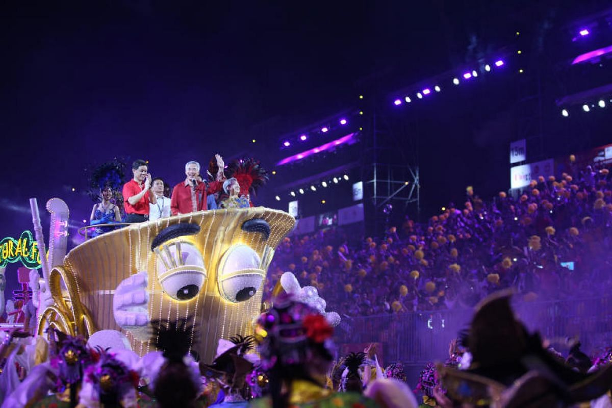 Prime Minister Lee Hsien Loong (centre), his wife Ho Ching (right) and Minister in the Prime Minister's Office Chan Chun Sing on board one of the nine floats.