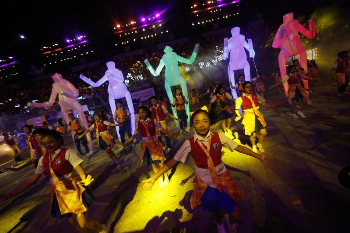 Young dancers perform in front of illuminated human figurines during the Chingay parade.