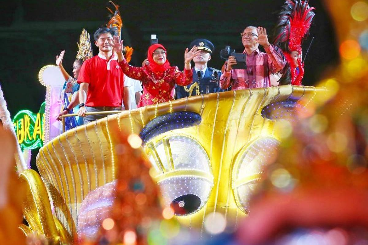 Mr Desmond Tan (left) People's Association chief executive director, standing together with President Halimah Yacob and Mr Mohamed Abdullah Alhabshee as they arrived on a float at the F1 Pit Building to the cheers of spectators at the Chingay 2018 pa