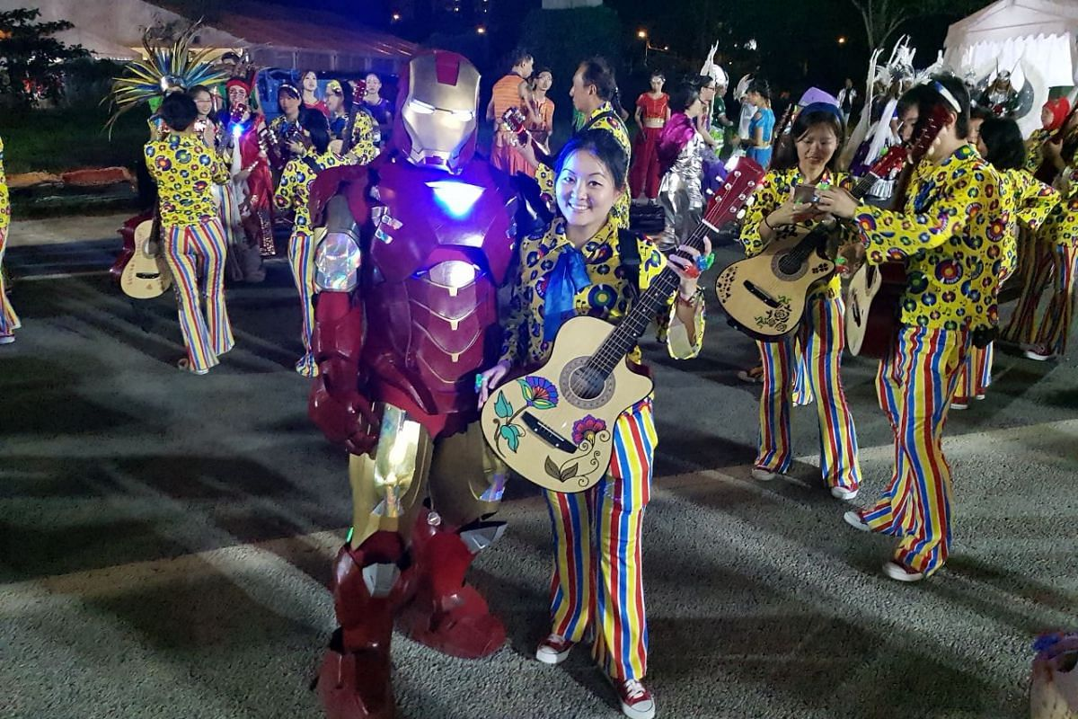 A performer from the guitar contingent with a cosplayer in an Iron Man suit at the Chingay parade.