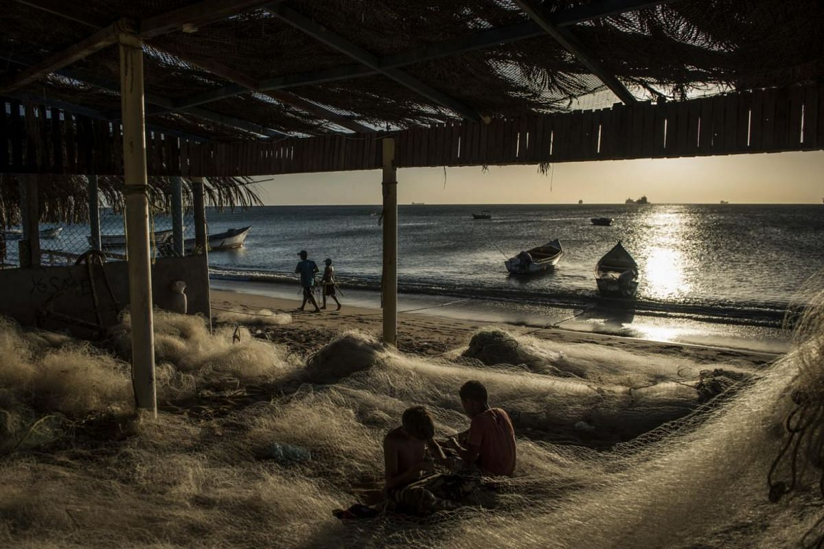 Boys repairing fishing nets damaged by an oil spill in Amuay, Venezuela.